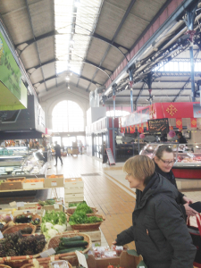 "The author (at right) shops at a ""bio,"" or organic, vegetable stall at Les Halles, as the arches of the 19th century iron structure are seen above."