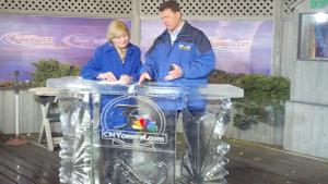 Laura Hand next to meteorologist Wayne Mahar, behind an ice set by carver Stan Koloko in 2015, just before Syracuse Winterfest.