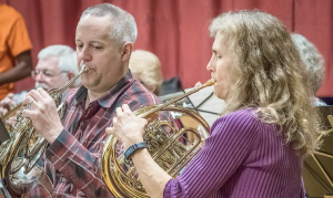 Musicians Ralph Schock on trumpet (background), and Loren Gosselin and Ruth Florey, playing French horns.