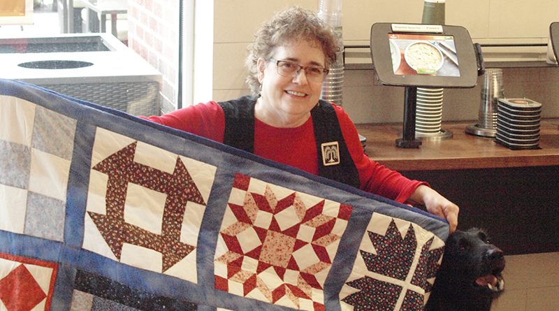 Laurie Leonard poses with her rendition of an underground railroad code quilt. Legend says quilts like these were put out to help lead escaped slaves to the North and freedom.