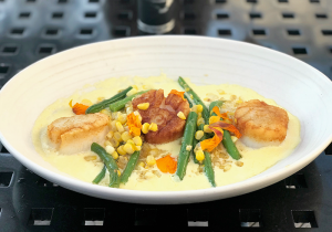 Three seared scallops are served on a sweet corn and truffle puree and topped with corn and summer beans.