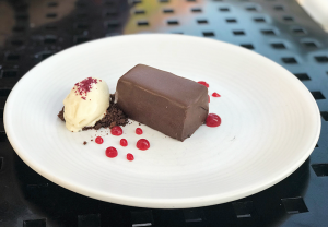 Chocolate torte filled with salted caramel and almonds and covered in chocolate. It's garnished with dulce de leche ice cream and hibiscus.