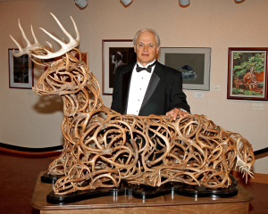 Tom Yacovella, wildlife artist, with his masterpiece, the famous whitetail scuplture.