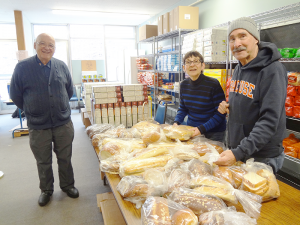 Ernie Wass (left) at the bread and cereal tables with fellow volunteers Debbie Goldman and Chet Machlin. Wass was an engineer at Bristol-Myers before he retired.