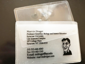 A small magnifier in a plastic sleeve with Marvin Druger's caricature and contact information on the sleeve. The author has given hundreds of magnifiers to people with whom he interacts.