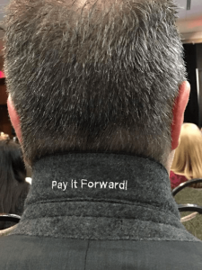 "The expression ""Pay it Forward"" embroidered on Mark Re's coat collar. He said that this notion is what motivates him to volunteer."