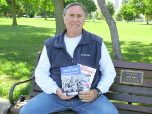 McCrobie at Breitbeck Park in Oswego, holding his two books, based on columns he has written for The Palladium-Times.