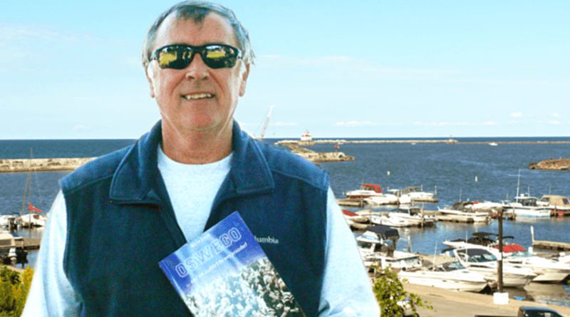Mike McCrobie, with the Oswego lighthouse in the background, holds his second book — 'We're from Oswego ... and we couldn't be any prouder!' — which was published in November.
