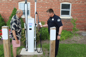 Mayor Platten with Patrolman Mike Grajko inspect a recently-installed charger for electric cars next to Jordan village hall.