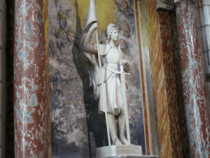 This statue of St. Joan of Arc, one of the patron saints of France, stands before an even older fresco, faded and damaged, but still beautiful after centuries. Photo By Bill Reed
