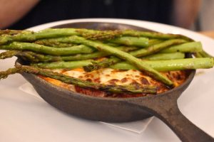 Eggplant involtini: Thin-sliced eggplant with ricotta cheese in a small skillet with tomato sauce and asparagus ($17).