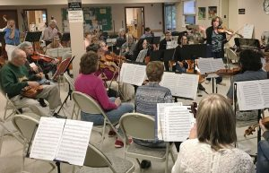 Edie Shillitoe, right, leads students during a recent rehearsal of Salt City New Horizons Orchestra