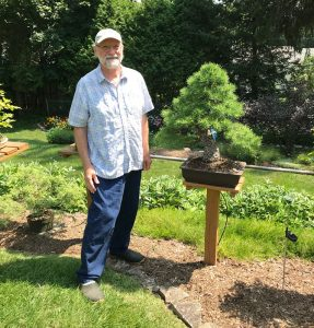 Carl Hoffner in front of one of his bonsai trees. He said some trees are decades old.