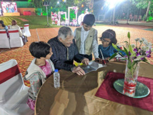 "Druger reading his book about ""Mr. Money and the Lucky Chicken""  to several Indian children at his grandson wedding in India."