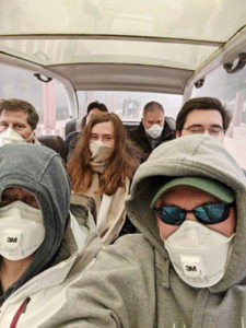 "The Druger family wearing respirator masks on a van in Dehli, India. ""The air pollution in Delhi was suffocating.  We had to wear masks all the time, and there was a smoggy mist, making buildings look surreal,"" Druger says."