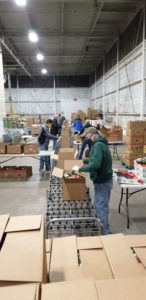 Packing food at Food Bank's warehouse in East Syracuse. Volunteers packed 9,000 food boxes in just one month, March.