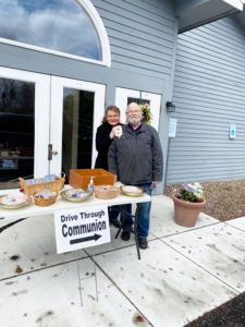 "Thea Smith and her husband, pastor Monte Smith, during a drive-through communion at North Syracuse Christian Church. ""If we don't [offer it], we feel something's missing,"" Thea Smith said."