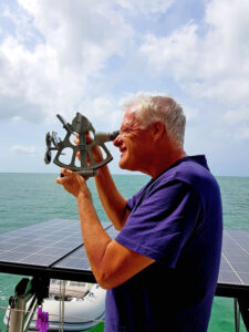 Simon Fowler checks the boat's position and charts how far they've come and how much of the voyage is left.