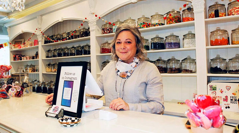Robin Mack stands at the register of her Sweet Dream Candy Shoppe, which she opened at 55 years old.