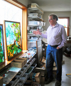 Robert Oddy, at his home studio on the east side of Syracuse, explains the work involved in two of his stained glass pieces.
