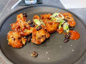Crispy cauliflower ($16 bathed in General Tso's sauce and graced with scallions and peanuts.