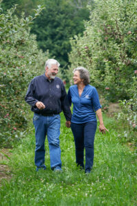 The Critzes Matthew and Juanita share a laugh together while roaming their apple orchard at Critz Farms.