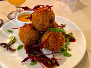 Octopus bombs are crispy coated balls of the cephalopod and spinach risotto. They are served with an eel and pineapple ghost sauce.