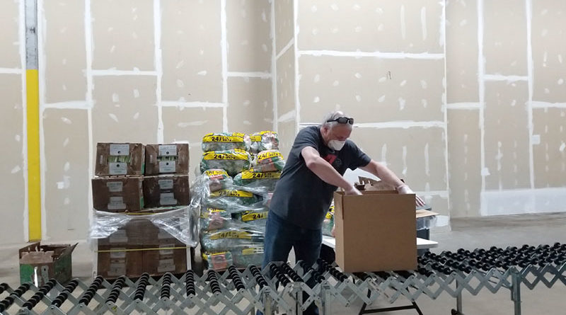 """Joe Wrobel of Liverpool, one of 800 volunteers who have kept the Food Bank of Central New York active during the pandemic. """"If you volunteer and do something for the community, helping others, you just get a great feeling,"""" he says."""
