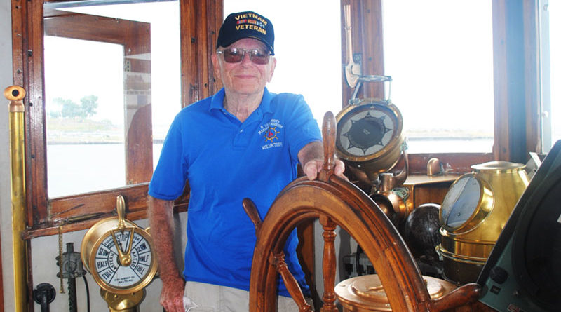 Volunteer Mike Brown at wheelhouse of U.S. Army LT-5 (Large Tug) at H. Lee White Maritime Museum in Oswego.